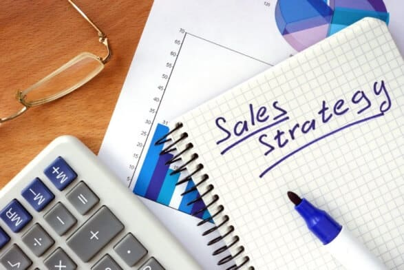 Sales strategy written in a notebook with charts to increase sales on a tight budget
