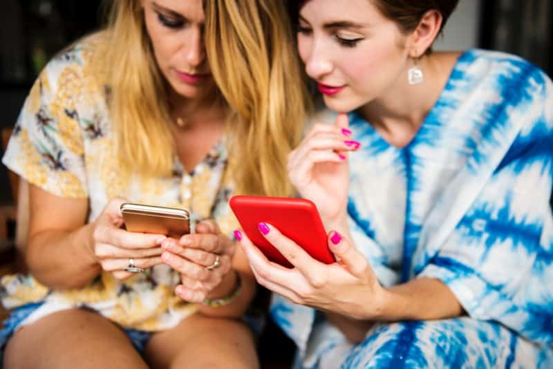two women both searching for the same thing and comparing what they see on their cell phone